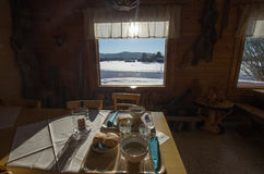 Sunny lunch with arctic view. On a wooden table a cosy lunch with a warm soup with the view of an arctic panorama outside the window Stock Photos