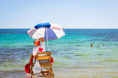 Sunny Mediterranean beach, lifeguard sitting in observation post Stock Image