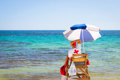 Sunny Mediterranean beach, lifeguard sitting in observation post Royalty Free Stock Photography
