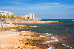 Sunny Mediterranean beach, Tourists relax on warm shore of sea Stock Image
