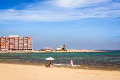 Sunny Mediterranean-Strand, Touristen entspannen sich auf Sand, Leute baden Lizenzfreie Stockfotografie