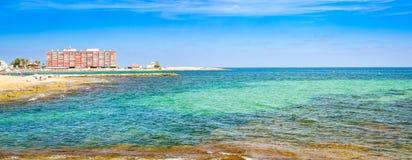 Sunny Mediterranean-Strand, Touristen entspannen sich auf Sand, Leute baden Lizenzfreie Stockfotos