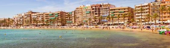 Sunny Mediterranean-Strand, Touristen entspannen sich auf Sand, Leute baden Stockbilder