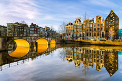 Sunny morning in Amsterdam, Netherlands. Sunny morning on a canal in Amsterdam, Netherlands with the sun shining below an arch bridge stock images
