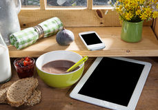 Sunny morning breakfast with digital tablet and mobile phone Royalty Free Stock Image