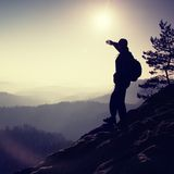 Sunny morning. Hiker is standing on the peak of rock in rock empires park and watch over misty and foggy morning valley Stock Photos