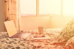 Sunny morning in modern apartment - open laptop on bed opposite window, next to cup of coffee and notebook. Beginning of the day. Concept of working at home stock photo