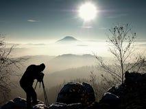 Sunny morning. Photographer preparing camera on tripod. Royalty Free Stock Photos