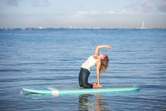 Sunny morning work out a pretty young woman in SUP Yoga back ben. Beautiful sunny morning work out a pretty young woman in SUP Yoga back bend stretch Pose in Ala Royalty Free Stock Images