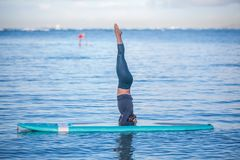 Sunny morning work out a pretty young woman in SUP Yoga practice