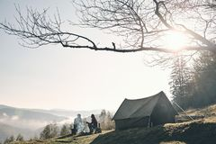 Sunny morning. Young couple having morning coffee while camping. In mountains Royalty Free Stock Photography