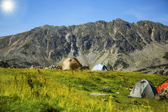 Sunny mountain alpine landscape with camping tents Stock Image