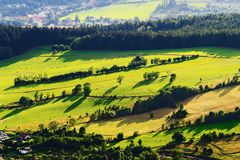 Sunny mountain valley with green fields and meadows. Scenic farmland landscape aerial view. Vast panorama of picturesque countryside in the Owl Mountains Gory Royalty Free Stock Image
