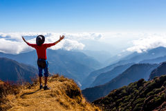 Sunny Mountains cloud Horizon and Hiker with Arms raised spread. Sunny Mountains Horizon View and Silhouette of happy excited Person staying on Cliff and making Royalty Free Stock Photography