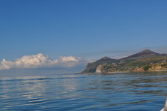 Sunny mountains sea scene with cloud bank Stock Image