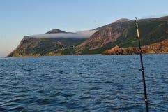 Sunny mountains sea scene fishing rod Royalty Free Stock Photography
