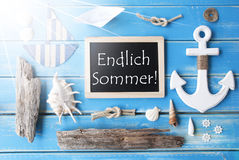 Sunny Nautic Chalkboard, Endlich Sommer Means Happy Summer. Flat Lay Of Chalkboard On Blue Wooden Background. Sunny Nautic Or Maritime Summer Decoration As Royalty Free Stock Image