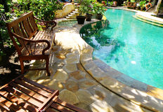 Sunny outdoor swimming pool and patio furniture. An image of a swimming pool with outdoor poolside patio furniture, surrounded by plantings of shrubs and trees Royalty Free Stock Photography