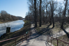 Sunny park with melting river during spring time Stock Image