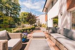 Sunny patio of modern house. Outdoor garden wicker furniture in sunny patio of modern house Royalty Free Stock Photo