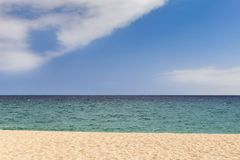 Sand sea sky. A sunny peaceful beach image with simple lines. Beach in the foreground, green sea and a blue sky with some clouds at the top. Plenty of copy space stock images