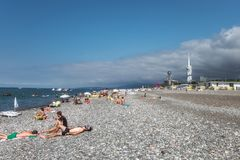 Batumi. Georgia - September 2, 2014. Black sea pebble beach with sunbathing people, Alphabeth tower and Technological royalty free stock photo
