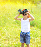 Sunny photo child boy looks in binoculars outdoors in summer. Day Royalty Free Stock Images