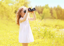 Sunny photo child looks in binoculars outdoors in warm summer. Day Stock Images
