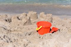 A sunny photo with a children`s beach pail and a spatula against a background of a sea Royalty Free Stock Image