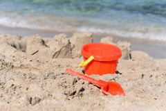 A sunny photo with a children`s beach pail and a spatula against a background of a sea Stock Photo