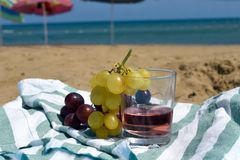 A sunny photo with a glass of wine and grapes against a background of a sand beach and sea. A sunny summer photo with a glass of wine and grapes against a stock photography
