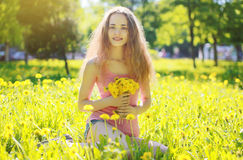 Sunny photo happy girl on yellow meadow with dandelions Stock Image