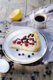Sunny Photo of morning breakfast in a rustic style. Cheesecake with raspberries and blueberries on wooden table Royalty Free Stock Photo