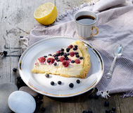 Sunny Photo with a morning breakfast in rustic style. Cheesecake raspberries and blueberries on wooden table. Sunny Photo with a morning breakfast in a rustic Stock Photos