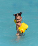 A sunny photo of a smiling little girl enjoying playing and swimming in the open pool stock photos