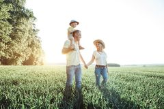 Sunny pictures of a happy family with a small child. Parents and son rest outside the city in the open air Stock Image