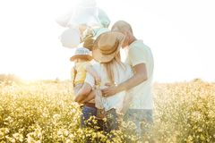Sunny pictures of a happy family with a small child in rape field. Parents and son rest outside the city in the open air Stock Photography