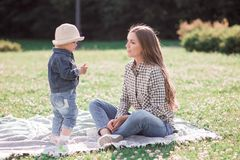 Sunny pictures of a happy little girl with mother. Walk on the grass, the sun is shining stock photos
