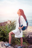 A sunny portrait of asian woman with backpack in white dress climbing on mountain near the sea Royalty Free Stock Image