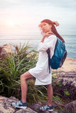 A sunny portrait of asian woman with backpack in white dress posing on stone near the sea royalty free stock image