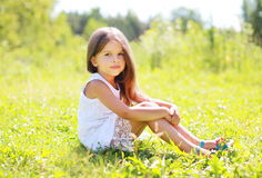 Sunny portrait of beautiful little girl sitting on the grass Royalty Free Stock Images