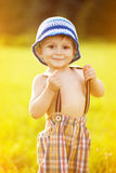 Sunny portrait of child. Portrait of adorable little boy holding his suspender pants royalty free stock photos