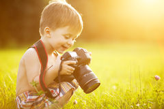 Sunny portrait of child with camera. Beautiful smiling kid boy holding a DSLR camera in park royalty free stock photos