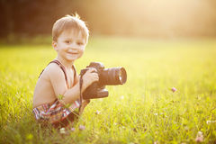 Sunny portrait of child with camera. Beautiful smiling kid boy holding a DSLR camera in park stock photos