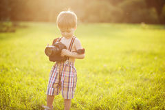 Sunny portrait of child with camera. Beautiful smiling kid boy holding a DSLR camera in park royalty free stock photo