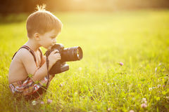 Sunny portrait of child with camera. Beautiful smiling kid boy holding a DSLR camera in park stock photography