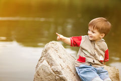 Sunny portrait of child at lake. Happy little boy sitting on a stone and pointing to the left royalty free stock image