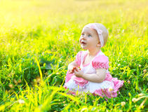 Sunny portrait of cute child on the grass in summer Stock Photo