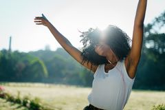 Sunny portrait in the field. Emotionaly dancing and shaking curly hair and hands african girl while enjoying music in Royalty Free Stock Photography