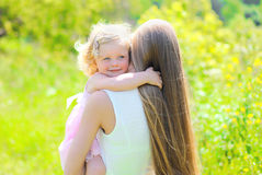 Sunny portrait of happy child hugging mother in summer Stock Images